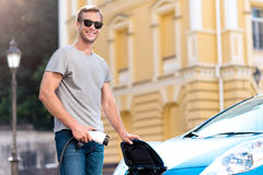 Man holding power connector for electric car. Look how to do it. Smiling contented young man with sunglasses looking at the camera while holding a power cable to Stock Image