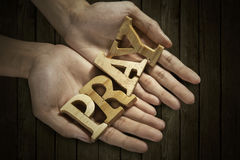 Man holding pray word in palm. With wooden background Stock Image