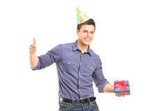 Man holding a present and giving thumb up Stock Images