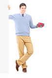 Man holding a present next to a blank panel Stock Photos
