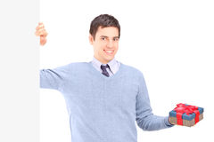 Man holding a present next to a panel Royalty Free Stock Image