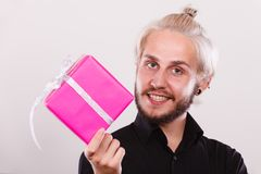Man holding present pink gift box in hand. People celebrating xmas, love and happiness concept - cool young man holding present pink gift box in hand Royalty Free Stock Photos