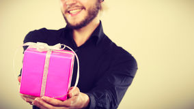 Man holding present pink gift box in hand. People celebrating xmas, love and happiness concept - cool young man holding present pink gift box in hand Stock Image