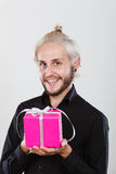 Man holding present pink gift box in hand. People celebrating xmas, love and happiness concept - cool young man holding present pink gift box in hand Royalty Free Stock Images