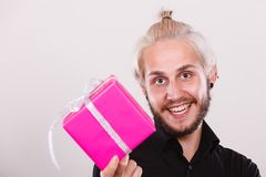 Man holding present pink gift box in hand. People celebrating xmas, love and happiness concept - cool young man holding present pink gift box in hand Stock Photo