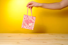 Man holding present in pink shopping bag Stock Photos