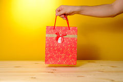 Man holding present in red shopping bag Royalty Free Stock Image