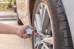 Man holding pressure gauge and checking air pressure of the car. Man holding pressure gauge and checking air pressure of his car Royalty Free Stock Image