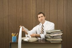 Man holding printout at desk Stock Images