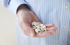 Man holding pumpkin seeds in hand. Recommended portion snack size of nuts for diabetic patients Royalty Free Stock Image
