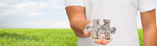 Man holding puzzle over natural background Stock Photography