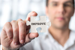 Man holding puzzle piece with word Improve Royalty Free Stock Photography