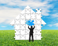 Man holding puzzles assembling for house shape. On meadow Stock Photos