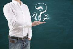 Man holding question marks. Man holding abstract drawn question marks on chalkboard background Royalty Free Stock Images