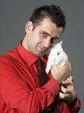 Man holding rabbit. Handsome young man holding baby rabbit Royalty Free Stock Photos