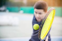Man holding racket about to hit a ball in tennis court royalty free stock photo