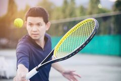 Man holding racket about to hit a ball in tennis court stock photography