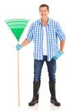 Man holding rake Stock Images