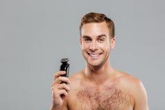 Man holding razor over gray background Royalty Free Stock Image