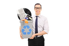 Man holding a recycle bin with bunch of old stuff Royalty Free Stock Images