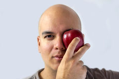 A man holding a red apple. With his hand and put it on his eye white background fruits natural Royalty Free Stock Photo
