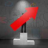 Man holding red arrow up on podium Royalty Free Stock Image