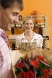Man holding red bouquet of flowers in flower shop, focus on florist in background, smiling, portrait Stock Photo