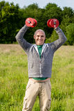 Man holding red dumbbells in the air Royalty Free Stock Photos
