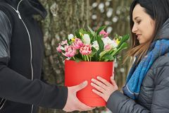 Man holding red gift box with beautiful bouquet of blooming pink, yellow and white tulips and white chrysanthemums with green leav. Man and girls with red gift Stock Photo