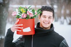 Man holding red gift box with beautiful bouquet of blooming pink, yellow and white tulips and white chrysanthemums with green leav. Es, romantic moment, woman Stock Images