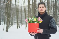 Man holding red gift box with beautiful bouquet of blooming pink, yellow and white tulips and white chrysanthemums with green leav. Es, romantic moment, woman Royalty Free Stock Images