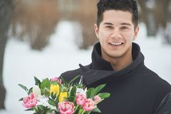 Man holding red gift box with beautiful bouquet of blooming pink, yellow and white tulips and white chrysanthemums with green leav. Es, romantic moment, woman Stock Image