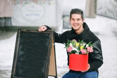 Man holding red gift box with beautiful bouquet of blooming pink, yellow and white tulips and white chrysanthemums with green leav. Es, outdoors, selective focus Royalty Free Stock Image