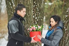 Man holding red gift box with beautiful bouquet of blooming pink, yellow and white tulips and white chrysanthemums with green leav. Man and girls with red gift Stock Images