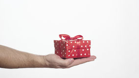 Man holding red gift box in his palm Stock Photo
