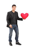 Man holding a red heart shaped pillow Stock Photo