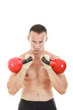 Man holding red kettlebells weights lifted and looking at the c Royalty Free Stock Photo