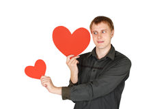Man holding red paper hearts and looking on it Royalty Free Stock Image