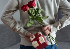 Man holding red rose flowers and gift box behind his back at home. Young modern and elegant man holding red rose flowers and gift box behind his back at home royalty free stock image
