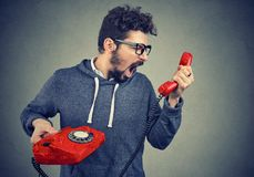 Man holding red telephone receiver and yelling in anger. Side view of casual bearded man holding red telephone receiver and yelling in anger Royalty Free Stock Photos