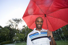 Man holding red umbrella outdoors, smiling, portrait Stock Image