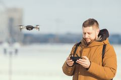 A man holding an remote control for the drone - managing the quadrocopter flight. Mid shot stock photo