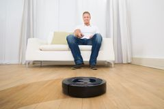 Man holding remote control of robotic vacuum cleaner Stock Images