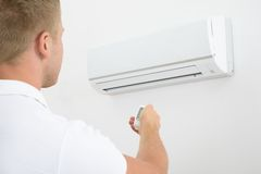 Man holding remote controller of air conditioner. Man Operating Air Conditioner With Remote Controller Stock Image