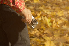 Man holding retro camera – yellow leaves in the background Stock Photography