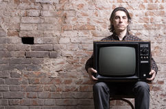 A man holding a retro television. Set sitting on a background of brick wall Royalty Free Stock Photography