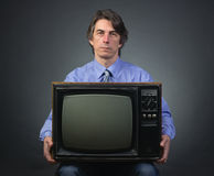A man holding a retro television. Set sitting on a dark background Stock Photo