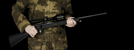 Man holding rifle isolated on black. Man dressed in camouflage holding .17 HMR rifle isolated on a black background royalty free stock photo