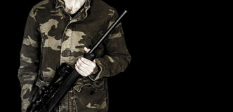 Man holding rifle isolated on black. Man dressed in camouflage holding .17 HMR rifle isolated on a black background stock photo