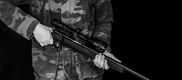 Man holding rifle isolated on black. Black and white photo of a man dressed in camouflage holding .17 HMR rifle isolated on a black background royalty free stock photography